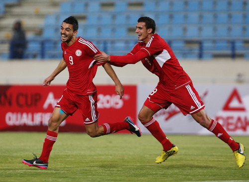 Lebanon's Mohammad Haidar, left, celebrates his goal with his teammate Hassan Chaito, during their game against Thailand of 2015 Asian Cup qualifier match, in Beirut, Lebanon, Friday March 22, 2013. Lebanon trounced Thailand 5-2 in a 2015 Asian Cup qualifier to give the country's football fans a much-needed morale boost after their sport was hit by a match-fixing scandal. (AP Photo/Hussein Malla)