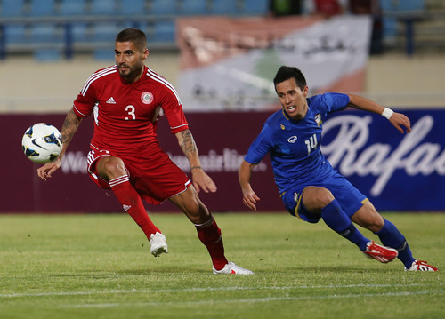 Lebanon's Yousef Mohammad, left, fights for the ball against Thailand's Anthony Ampaipitakwong, during the 2015 Asian Cup qualifier match, in Beirut, Lebanon, Friday March 22, 2013. Lebanon trounced Thailand 5-2 in a 2015 Asian Cup qualifier to give the country's football fans a much-needed morale boost after their sport was hit by a match-fixing scandal. (AP Photo/Hussein Malla)