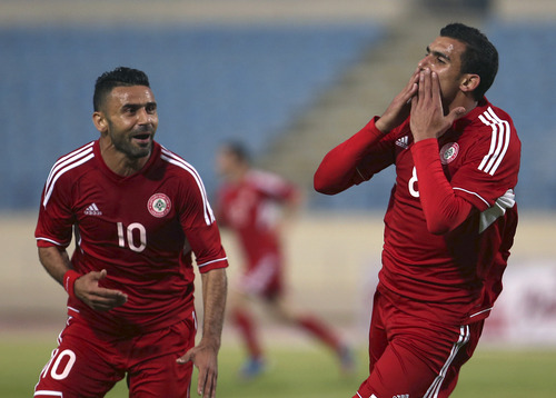 Lebanon's Hassan Chaito, right, celebrates with his teammate Abbas Atwi, left, his second goal against Thailand, during the 2015 Asian Cup qualifier match, in Beirut, Lebanon, Friday March 22, 2013. Lebanon trounced Thailand 5-2 in a 2015 Asian Cup qualifier to give the country's football fans a much-needed morale boost after their sport was hit by a match-fixing scandal. (AP Photo/Hussein Malla)