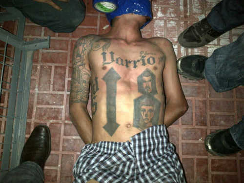 """FILE - In this undated file image obtained by the Associated Press on Feb. 14, 2013, a man lies on the ground surrounded by unidentified people. On Jan. 9, 2013, neighbors of Kevin Said Carranza Padilla, 28, known in the gang world as """"Teiker,"""" saw police come and take him and his girlfriend without a shot. The next morning, Jan. 10, Honduras' major newspaper, El Heraldo, reported that police had captured Carranza in connection with the murder of a police commander months earlier, publishing this photo of a shirtless, tattooed young man lying on the ground, his hands behind his back, his face partially wrapped in blue duct tape, the roll still attached. Carranza's mother, Blanca Alvarado, recognized him from his tattoos. (AP Photo, File)"""