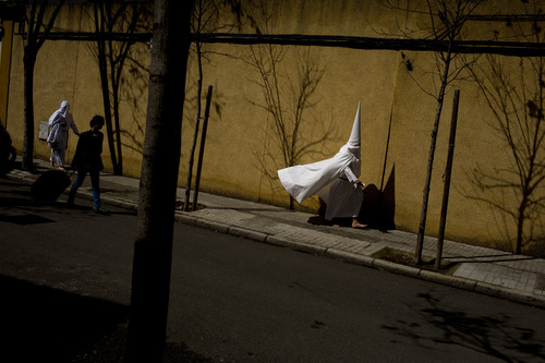 Hooded penitents from the La Paz brotherhood walk to the church to take part in a procession in Seville, Spain, Sunday, March 24, 2013. Hundreds of processions take place throughout Spain during the Easter Holy Week. (AP Photo/Emilio Morenatti)