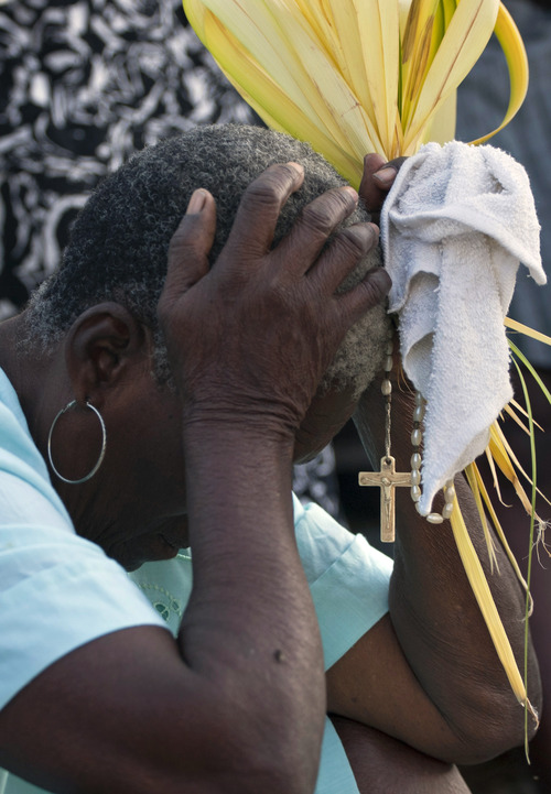 A woman holds palm fronds and a rosary while praying during an outdoor Palm Sunday Mass at an earthquake-damaged cathedral in Port-au-Prince, Haiti, Sunday, March 24, 2013. Christians from around the world commemorate Palm Sunday as they celebrate Jesus Christ's triumphant entry into the holy city of Jerusalem 2,000 years ago. (AP Photo/Dieu Nalio Chery)