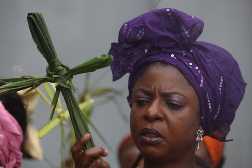 A woman holds palm leaves in the shape of a cross during a Christian Palm Sunday procession in Lagos, Nigeria, Sunday, March 24, 2013. Palm Sunday marks the sixth and last Sunday of the Christian Holy month of Lent and the beginning of Holy Week. (AP Photo/Sunday Alamba)