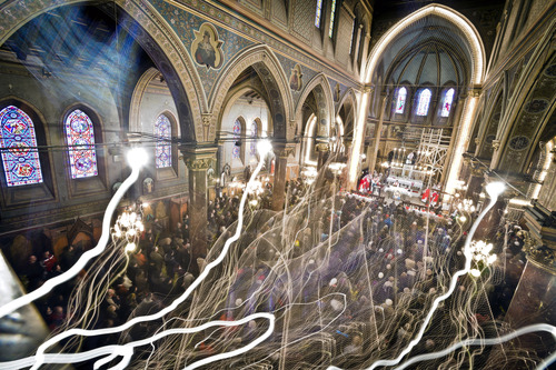 A photograph taken with a long exposure shows Romanian Catholic worshipers attend a Palm Sunday religious service at the St. Joseph cathedral in Bucharest, Romania, Sunday, March 24, 2013.(AP Photo/Vadim Ghirda)