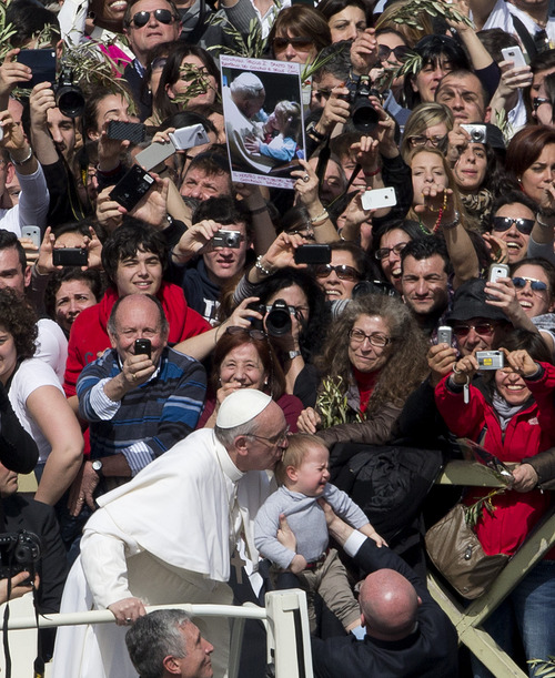 Pope Francis kisses a baby after celebrating his first Palm Sunday Mass, in St. Peter's Square, at the Vatican, Sunday, March 24, 2013. Pope Francis celebrated his first Palm Sunday Mass in St. Peter's Square, encouraging people to be humble and young at heart, as tens of thousands joyfully waved olive branches and palm fronds. The square overflowed with some 250,000 pilgrims, tourists and Romans eager to join the new pope at the start of solemn Holy Week ceremonies, which lead up to Easter, Christianity's most important day (AP Photo/Alessandra Tarantino)