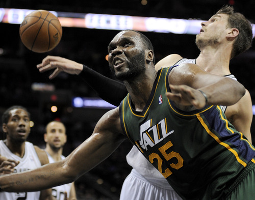 Utah Jazz's Al Jefferson (25) collides with San Antonio Spurs' Tiago Splitter, of Brazil, during the first half of an NBA basketball game, Friday, March 22, 2013, in San Antonio. San Antonio won 104-97 in overtime. (AP Photo/Darren Abate)