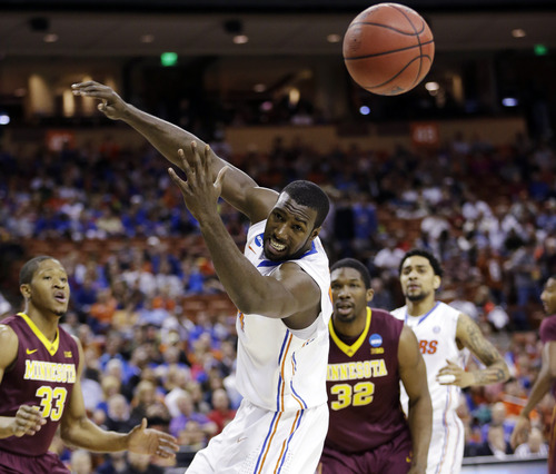 Florida's Patric Young, center, loses cotrol of a pass as Minnesota's Rodney Williams (33) and Trevor Mbakwe (32) watch during the first half of a third-round game of the NCAA college basketball tournament, Sunday, March 24, 2013, in Austin, Texas. (AP Photo/Eric Gay)