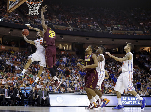 Florida's Mike Rosario, left, is fouled by Minnesota's Trevor Mbakwe (32) as he tries to score during the first half of a third-round game of the NCAA college basketball tournament, Sunday, March 24, 2013, in Austin, Texas. (AP Photo/Eric Gay)