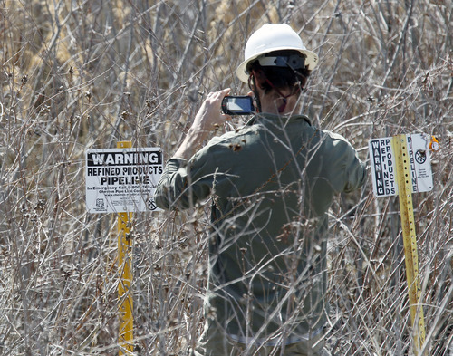 Al Hartmann  |  The Salt Lake Tribune A man photographs a pipeline sign near a petroleum spill in a wetland area between Willard Bay North Marina and I-15 Tuesday March 19. The leak was detected Monday. Authorities said the leak was contained in retaining ponds and none went into Willard Bay.