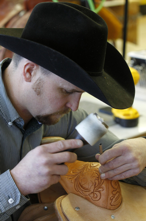 Al Hartmann  |  The Salt Lake Tribune Matt Warner, head of design, stamps a floral pattern into the leather on the swell of a custom-made saddle at Burns Saddlery shop in Salina.