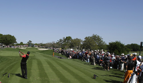Tiger Woods, left, hits from the seventh tee during the final round of the Arnold Palmer Invitational golf tournament, Monday, March 25, 2013, in Orlando, Fla. (AP Photo/John Raoux)