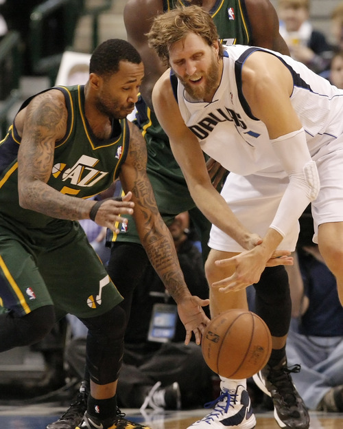 Utah Jazz guard Mo Williams (5) steals the ball away from Dallas Mavericks forward Dirk Nowitzki (41) during the first half of an NBA basketball game on Sunday, March 24, 2013, in Dallas. (AP Photo/Brandon Wade)