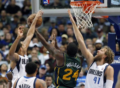 Utah Jazz forward Paul Millsap (24) shoots as Dallas Mavericks forwards Brandan Wright (34) and Dirk Nowitzki (41) defend during the second half of an NBA basketball game, Sunday, March 24, 2013, in Dallas. Dallas won 113-108. (AP Photo/Brandon Wade)