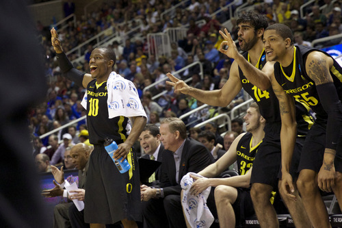 Oregon guard Johnathan Loyd (10), forward Ben Carter (32), forward Arsalan Kazemi (14) and center Tony Woods (55) react as guard Damyean Dotson, not shown, hits a 3-pointer against Saint Louis during their third-round game in the NCAA college basketball tournament, Saturday, March 23, 2013, in San Jose, Calif. Oregon won 74-57. (AP Photo/The Oregonian, Bruce Ely)  MAGS OUT; TV OUT; LOCAL TV OUT; LOCAL INTERNET OUT; THE MERCURY OUT; WILLAMETTE WEEK OUT; PAMPLIN MEDIA GROUP OUTMAGS