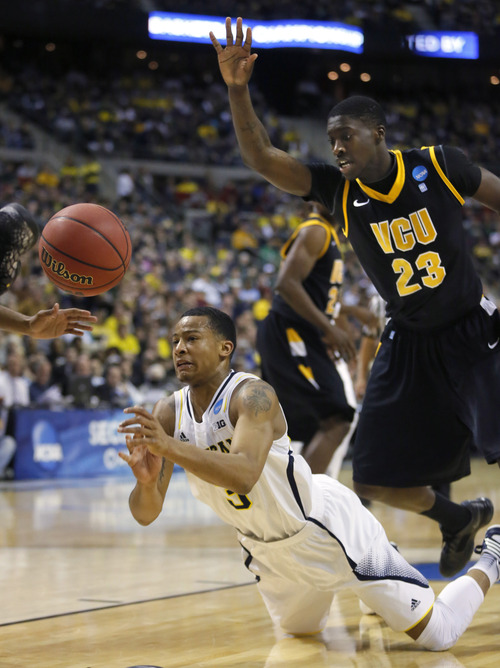 Michigan guard Trey Burke (3) manages to pass the ball against Virginia Commonwealth forward Jarred Guest (23) in the second half of a third-round game of the NCAA college basketball tournament Saturday, March 23, 2013, in Auburn Hills, Mich. Michigan defeated Virginia Commonwealth 78-53. (AP Photo/Duane Burleson)