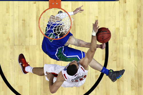 San Diego State's JJ O'Brien, bottom, blocks a shot by Florida Gulf Coast's Brett Comer during the first half of a third-round game of the NCAA college basketball tournament, Sunday, March 24, 2013, in Philadelphia. (AP Photo/Matt Slocum)
