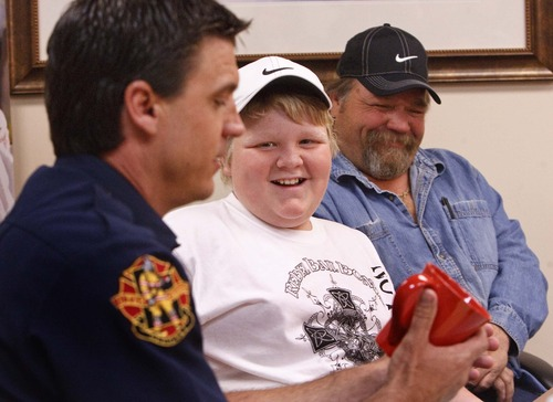 Leah Hogsten  |  The Salt Lake Tribune Twelve-year-old C.J. Saulsgiver of Roy performed CPR on his mother to save her life on his birthday. C.J. and his father, Doc Saulsgiver, laugh as Roy Fire Department Chief Jason Poulsen presents the boy with gifts from the firehouse Friday at McKay-Dee Hospital. C.J. learned the skill only months ago through a foster care safety training course.