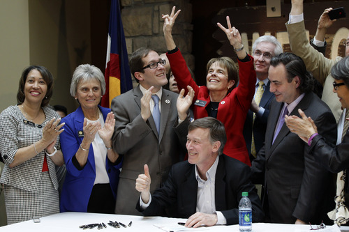 FILE – In this March 21, 2013 file photo Colorado Gov. John Hickenlooper gives a thumbs up as he celebrates with members of the legislature after signing the Civil Unions Act into law at the Colorado History Museum in Denver. The Supreme Court can choose from a wide array of outcomes in ruling on California's Proposition 8 ban on same-sex marriage and the federal Defense of Marriage Act (DOMA), which defines marriage as the union of a man and a woman. The cases will be argued Tuesday, March 26, 2013, and Wednesday; rulings are not likely before late June. (AP Photo/Brennan Linsley, File)