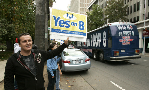 "FILE - In this Nov. 3, 2008, file photo a man holds up a ""Yes on 8"" sign as a bus passes, bearing another sign to ""Vote No On Prop 8"" in Sacramento, Calif. The Supreme Court can choose from a wide array of outcomes in ruling on California's Proposition 8 ban on same-sex marriage and the federal Defense of Marriage Act (DOMA), which defines marriage as the union of a man and a woman. The cases will be argued Tuesday, March 26, 2013, and Wednesday; rulings are not likely before late June. (AP Photo/Rich Pedroncelli, File)"