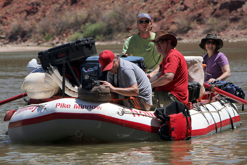 Francisco Kjolseth  |  The Salt Lake Tribune River guide Justin Malloy, in back, man's the oars on the KUED video boat of the day as videographer Gary Turnier films a shot alongside audio engineer Kevin Sweet, center right, and producer Nancy Green while filming on the Colorado river in the summer of 2012.