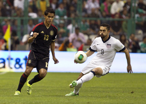 United States' Herculez Gomez, right, and Mexico's  Severo Meza vie for the ball during a 2014 World Cup qualifying match at the Aztec stadium in Mexico City, Tuesday, March 26, 2013. (AP Photo/Christian Palma)