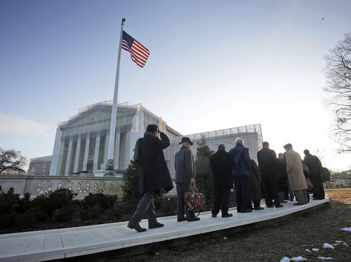People make their way inside into the Supreme Court in Washington, Tuesday, March 26, 2013, for the court's hearing on California's voter approved ban on same-sex marriage, Proposition 8. (AP Photo/Pablo Martinez Monsivais)
