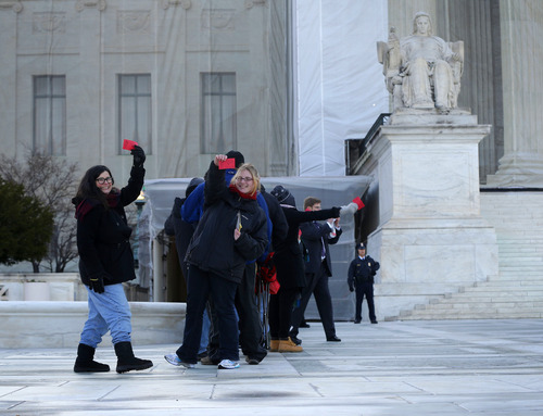 People hold up their tickets that had been issued to the general public for entrance Supreme Court in Washington, Tuesday, March 26, 2013, for the court's hearing on California's voter approved ban on same-sex marriage. Some people waited in line _ even through light snow _ since Thursday for the coveted seats for the argument over California's Proposition 8.  (AP Photo/Pablo Martinez Monsivais)
