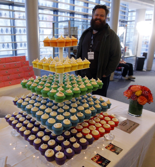 FILE - In this Dec. 9, 2012 file photo, a wedding cake made of rainbow-colored layers of cupcakes waits for newlyweds in a reception area at Seattle City Hall, where some of the first gay couples to legally wed in the state took their vows. On Tuesday, the US Supreme Court will begin hearing two days of cases involving gay marriage. (AP Photo/Elaine Thompson)