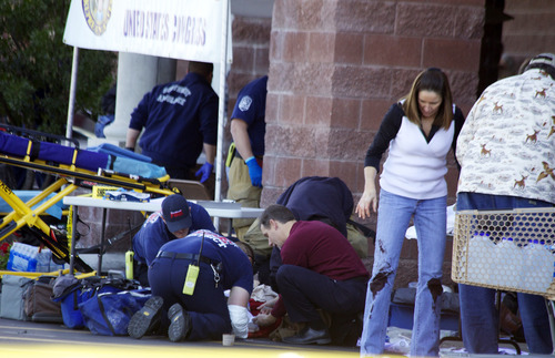 FILE - In this Jan. 8, 2011 file photo, emergency personnel attend to a shooting victim outside a shopping center in Tucson, Ariz., where U.S. Rep. Gabrielle Giffords, D-Ariz., and others were shot as the congresswoman was meeting with constituents. Hundreds of pages of police reports in the investigation of the Tucson shooting rampage that wounded former Rep. Gabrielle Giffords were released Wednesday, March 27, 2013 marking the public's first glimpse into documents that authorities have kept private since the attack more than two years ago.  (AP Photo/James Palka, File)