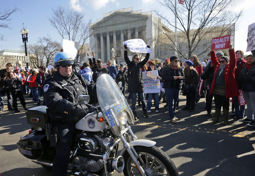Demonstrator stand outside the Supreme Court in Washington, Tuesday, March 26, 2013, as the court hears arguments on California's voter approved ban on same-sex marriage, Proposition 8. (AP Photo/Pablo Martinez Monsivais)