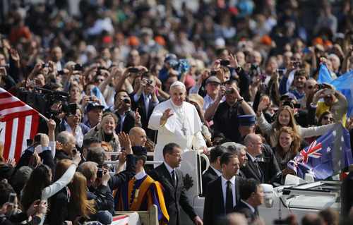 Pope Francis is driven through the crowd during his first general audience, in St. Peter's Square, at the Vatican, Wednesday, March 27, 2013. Francis has called for an end to the violence and looting that has accompanied the weekend coup in the Central African Republic in his first such appeal for peace since becoming pope. (AP Photo/Andrew Medichini)