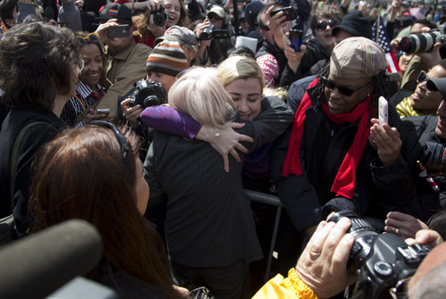 Plaintiff Edith Windsor, of New York, back to camera, is hugged and greeted by supporters in front of the Supreme Court in Washington, Wednesday, March 27, 2013, after the court heard arguments on the Defense of Marriage Act (DOMA) case. The U.S. Supreme Court, in the second day of gay marriage cases, turned Wednesday to a constitutional challenge to the federal law that prevents legally married gay Americans from collecting federal benefits generally available to straight married couples. (AP Photo/Carolyn Kaster)
