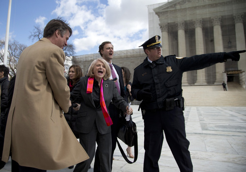 Plaintiff Edith Windsor,of New York is helped by security in front of the Supreme Court in Washington, Wednesday, March 27, 2013, after the court heard arguments on the Defense of Marriage Act (DOMA) case. The U.S. Supreme Court, in the second day of gay marriage cases, turned Wednesday to a constitutional challenge to the federal law that prevents legally married gay Americans from collecting federal benefits generally available to straight married couples. (AP Photo/Carolyn Kaster)