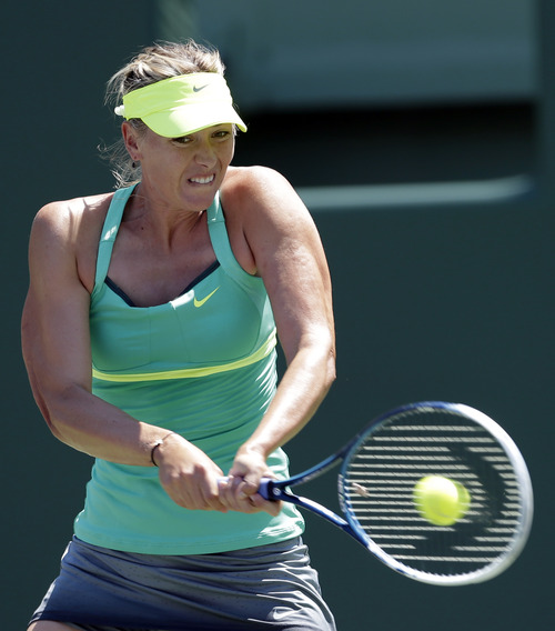 Maria Sharapova, of Russia, returns to Jelena Jankovic, of Serbia, during the semifinals of the Sony Open tennis tournament in Key Biscayne, Fla., Thursday, March 28, 2013. (AP Photo/Alan Diaz)