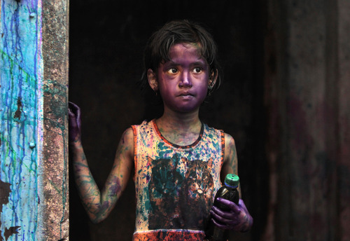 A Bangladeshi Hindu child smeared in colors stands at a doorway during Holi festival celebrations in Dhaka, Bangladesh, Thursday, March 28, 2013. Hindus celebrate Holi, the festival of colors, by painting each other in bright pigments, distributing sweets and squirting water at one another. The holiday celebrated mainly in India and Nepal marks the beginning of spring and the triumph of good over evil.   (AP Photo/A.M. Ahad)