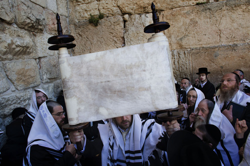 Ultra Orthodox Jewish men hold up a Torah scroll as they pray during the Passover Holiday in the Western Wall, the holiest site where Jews can pray in Jerusalem's old city, Thursday, March 28, 2013. The Passover holiday celebrates the biblical story of the Israelites' escape from slavery and exodus from Egypt. (AP Photo/Bernat Armangue)