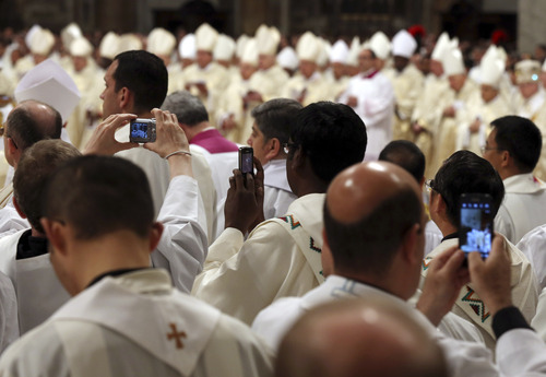 Priests take pictures as Pope Francis celebrates the Chrism Mass in St. Peter's Basilica at the Vatican, Thursday, March 28, 2013. The Chrism Mass marks the start of the Easter celebrations. (AP Photo/Gregorio Borgia)
