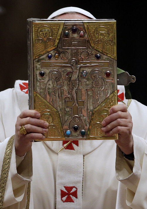 Pope Francis holds up a copy of the book of the gospel during a Chrism Mass in St. Peter's Basilica at the Vatican, Thursday, March 28, 2013. The Chrism Mass marks the start of the Easter celebrations. (AP Photo/Gregorio Borgia)
