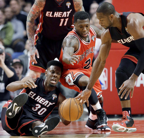 Miami Heat guards Norris Cole (30) and Dwyane Wade, right, scramble for a loose ball against Chicago Bulls guard Nate Robinson during the first half of an NBA basketball game in Chicago on Wednesday, March 27, 2013. (AP Photo/Nam Y. Huh)