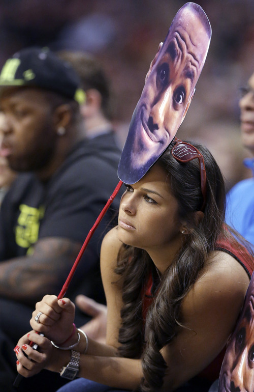 A fan holds up a cutout image of Miami Heat's LeBron James as she watches the first half of an NBA basketball game between the Heat and the Chicago Bulls in Chicago on Wednesday, March 27, 2013. (AP Photo/Nam Y. Huh)