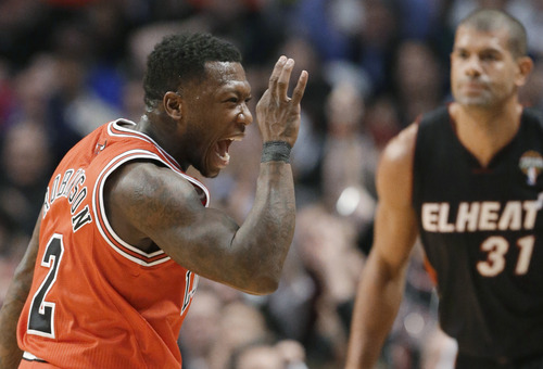 Chicago Bulls guard Nate Robinson, left, celebrates a 3-point shot, as Miami Heat forward Shane Battier watches during the first half of an NBA basketball game in Chicago on Wednesday, March 27, 2013. (AP Photo/Nam Y. Huh)