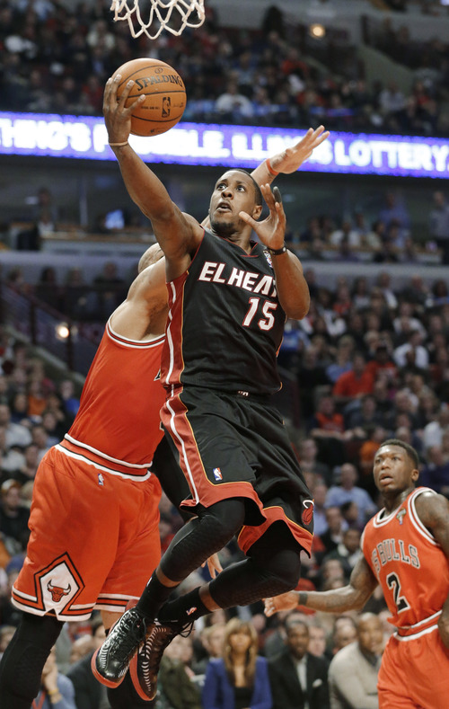 Miami Heat guard Mario Chalmers (15) drives to the basket past Chicago Bulls forward Carlos Boozer during the first half of an NBA basketball game in Chicago on Wednesday, March 27, 2013. (AP Photo/Nam Y. Huh)