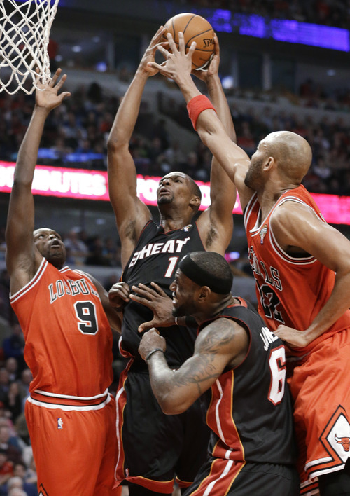 Miami Heat center Chris Bosh (1) shoots between Chicago Bulls forward Luol Deng, left, and forward Taj Gibson during the first half of an NBA basketball game in Chicago on Wednesday, March 27, 2013. Miami's LeBron James is at center right. (AP Photo/Nam Y. Huh)