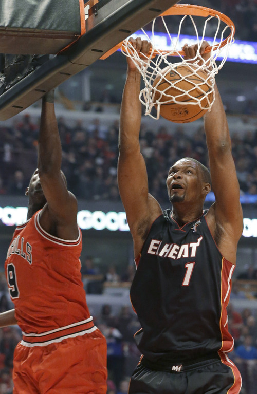 Miami Heat center Chris Bosh, right, dunks against Chicago Bulls forward Luol Deng during the first half of an NBA basketball game in Chicago on Wednesday, March 27, 2013. (AP Photo/Nam Y. Huh)