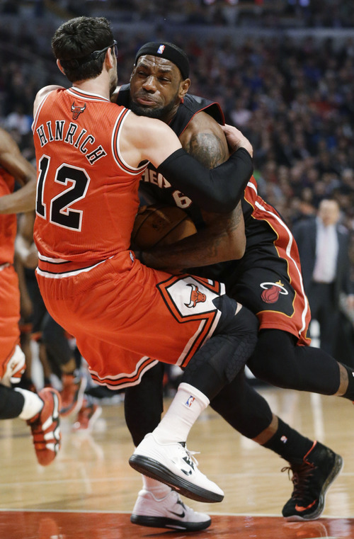 Miami Heat forward LeBron James, right, drives as Chicago Bulls guard Kirk Hinrich fouls him during the first half of an NBA basketball game in Chicago on Wednesday, March 27, 2013. (AP Photo/Nam Y. Huh)