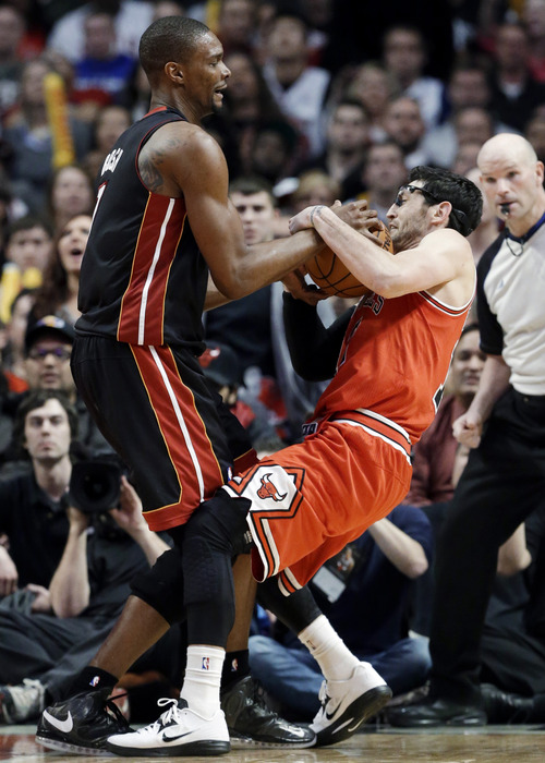 Chicago Bulls guard Kirk Hinrich, right, and Miami Heat center Chris Bosh wrestle for a rebound during the second half of an NBA basketball game in Chicago on Wednesday, March 27, 2013. The Bulls won 101-97, ending the Heat's 27-game winning streak. (AP Photo/Nam Y. Huh)