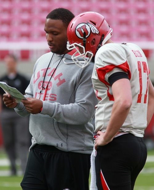 "Leah Hogsten  |  The Salt Lake Tribune University of Utah football team's Brian Johnson runs through plays with  quarterback Logan Bateman during the Utes practice, Tuesday, March 26, 2013. Johnson has been demoted from offensive coordinator, but still coaches the quarterbacks as the ""co-coordinator"" with the newly hired Dennis Erickson."