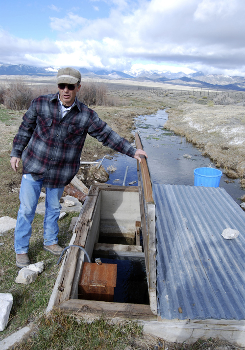 Brian Maffly | The Salt Lake Tribune  Dave Baker examines a monitoring station on a tiny spring that feeds his family's sprawling Snake Valley ranch. Data from this and dozens of other monitors is intended to guide controversial groundwater development proposed by Las Vegas.