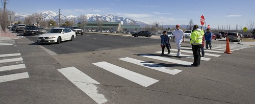 Paul Fraughton  |   Salt Lake Tribune Crossing guards help children across 6200 South  at an intersection near Westbrook Elementary School. Funding was made available for a pedestrian bridge near the school as well as  a new signalized  intersection.  Tuesday, March 19, 2013