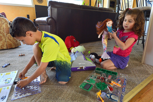 Lucas Dolan, 7, left, starts to build a science project from a kit,  while his sister Lilli Ana Dolan, 5, plays with her dolls and other girl's toys inside their home in Pleasant Hill, Calif., on Thursday, March 21, 2013. (Dan Rosenstrauch/Staff)